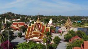Буддийский висок около озера Взгляд сверху трутня крыш и статуй чудесного буддийского виска расположенного около озера на солнечн сток-видео