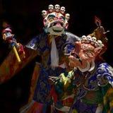 2 буддийских монаха в старых ритуальных масках: белая маска Mahakala и оранжевая маска Makar, маски украшены с smal Стоковая Фотография
