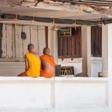 2 буддийских монаха на крылечке здания, Louangphabang, Стоковое фото RF
