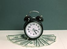 Будильник и деньги долларов стога на таблице Концепция банковского дела для спасения Стоковые Изображения