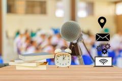 будильник и книга и соединяют сеть образования значка в нерезкости предпосылки конференц-зала с космосом экземпляра Стоковое Изображение RF