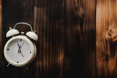 Будильник показывая часы почти 12 o, на старой деревянной предпосылке пола стоковое фото