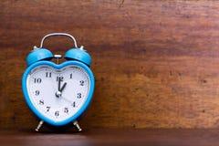 Будильник сердца форменный на деревянной предпосылке Один час o стоковая фотография rf