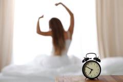 Будильник стоя на прикроватном столике имеет уже звенел рано утром для того чтобы проспать вверх по женщине в кровати сидя в пред стоковая фотография rf