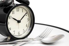 Будильник с вилкой и нож на плите на белизне съешьте время к еда принципиальной схемы здоровая стоковое изображение rf