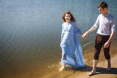 Будущая мама и папа идя на воду вдоль берега реки держа руки совместно Стоковое фото RF