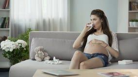 Будущая мать используя ткани для того чтобы дунуть душный нос, чувствуя ее лоб, холодный акции видеоматериалы