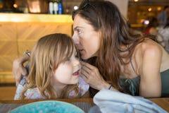 Будьте матерью говорить секрет в ухе к девушке в ресторане Стоковое Изображение