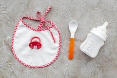 Будьте матерью грудного молока заботы в еде бутылки и младенца напудренной формулой здоровой с bib для младенца подавая на каменн Стоковая Фотография