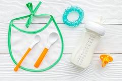 Будьте матерью грудного молока заботы в еде бутылки и младенца напудренной формулой здоровой с bib для младенца подавая на белой  Стоковая Фотография