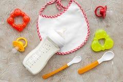 Будьте матерью грудного молока заботы в еде бутылки и младенца напудренной формулой здоровой с bib для младенца подавая на каменн Стоковое Изображение RF