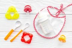 Будьте матерью грудного молока заботы в еде бутылки и младенца напудренной формулой здоровой с bib для младенца подавая на белой  Стоковые Фото
