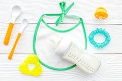 Будьте матерью грудного молока заботы в еде бутылки и младенца напудренной формулой здоровой с bib для младенца подавая на белой  Стоковые Изображения