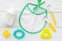 Будьте матерью грудного молока заботы в еде бутылки и младенца напудренной формулой здоровой с bib для младенца подавая на белой  Стоковое Фото