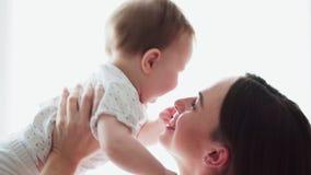 Будьте матерью держать прелестного младенца в оружиях и играть с ним на белой предпосылке сток-видео