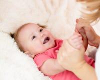 Будьте матерью держать руки ее ребенка лежа на кровати стоковая фотография rf