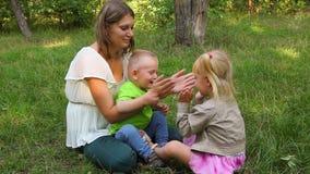 Будьте матерью играть при ее дети, мальчик и девушка имея потеху сток-видео