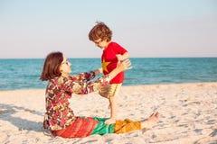 Будьте матерью игр с ее младенцем на пляже Стоковая Фотография RF