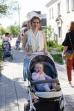 Будьте матерью идти в улицу с ее младенцем в прогулочной коляске стоковое фото