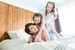 Будьте матерью и 2 дет в спальне на кровати Стоковое Фото