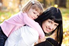 Будьте матерью и ее дочь лежа на leav осени Стоковые Изображения