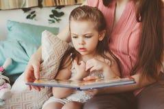 Будьте матерью книги чтения к дочери малыша в спальне на спокойная ночь Вскользь захват образа жизни счастливой семьи Стоковая Фотография RF