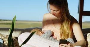Будьте матерью кормить ее младенца грудью пока использующ мобильный телефон 4k сток-видео