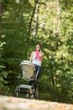 Будьте матерью нажатия pram или детской дорожной коляски вдоль сельского throug дороги Стоковая Фотография RF