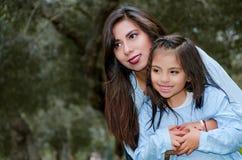 Будьте матерью носить ее милую и усмехаясь дочь в парке стоковое фото