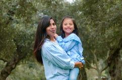 Будьте матерью носить ее милую и усмехаясь дочь в парке стоковые изображения rf