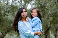Будьте матерью носить ее милую и усмехаясь дочь в парке стоковое фото rf