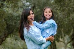 Будьте матерью носить ее милую и усмехаясь дочь в парке стоковые фото