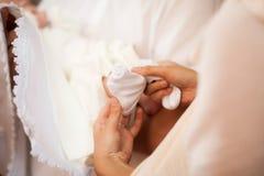 Будьте матерью одевать ногу мальчика с белым носком в церков Стоковые Фотографии RF