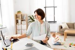 Будьте матерью работы на компьтер-книжке и младенце играя дома стоковое изображение rf