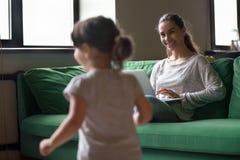 Будьте матерью работы на компьтер-книжке пока девушка ребенк играя дома стоковые фото