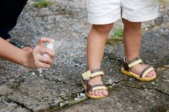 Будьте матерью распыляя репеллентов насекомого или москита на девушке кожи, репелленте москита для младенцев, малышей которые защ Стоковая Фотография RF