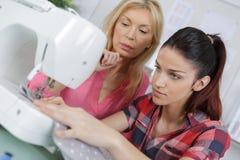 Будьте матерью уча дочери как использовать швейную машину Стоковое Изображение