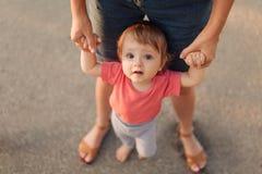 Будьте матерью уча первых шагов дочери младенца снаружи в заходе солнца Стоковые Фото