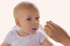 Будьте матерью feedding ее малыш одного года белокурый голубоглазый с югуртом стоковая фотография rf