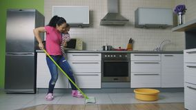 Будьте матерью mopping пол и танцевать держащ младенца сток-видео