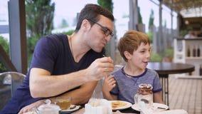 Будьте отцом давать вкус к сыну пока обедающ в кафе совместно сток-видео