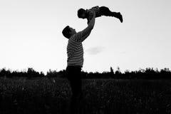 Будьте отцом играть с его маленьким сыном в поле цветка на заходе солнца Человек бросает вверх мальчика Стоковые Изображения RF