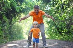 Будьте отцом игры с его маленьким сыном в парке лета Мальчик бежит прочь, и его папа улавливает его Одежда взгляда семьи стоковая фотография rf