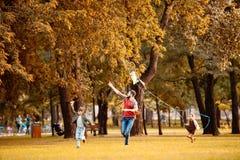 Будьте отцом и 2 дет бежать через парк и летать осени Стоковое фото RF