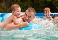 Будьте отцом и его дети имея потеху в бассеине Стоковые Фото