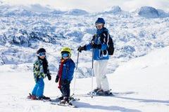 Будьте отцом и 2 мальчика, катаясь на лыжах на солнечный день на саммите горы Стоковые Фото