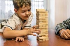 Будьте отцом и сфокусировал сына играя игру jenga дома стоковые изображения rf