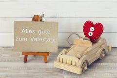 Будьте отцом карточки дня ` s с миниатюрным мольбертом и деревянным автомобилем немецко стоковая фотография
