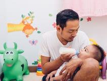 Будьте отцом молока действующей мамы подавая его младенец сына 1-ти летний на стуле стоковые изображения rf