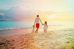 Будьте отцом при 2 дет идя на пляж на заходе солнца Стоковые Изображения